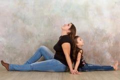 Den gulliga lilla flickan och hennes härliga barn fostrar att sitta tillsammans på golvet Royaltyfria Foton