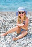 Den gulliga lilla flickan på stranden rymmer i handstenarna med ima arkivbild