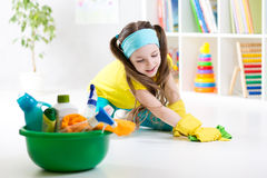 Den gulliga lilla flickan rentvår ett golv Royaltyfri Fotografi