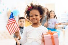 Den gulliga lilla flickan rymmer en gåva och en flagga av USA på berömmen av hennes födelsedag arkivfoto