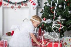 Den gulliga lilla flickan söker efter gåvor under ny jaröst för jul Fotografering för Bildbyråer
