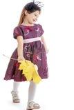 Den gulliga lilla flickan samlar gula lönnlöv Royaltyfri Foto