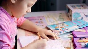 Den gulliga lilla flickan skriver henne läxa på tabellen stock video