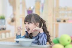 Den gulliga lilla flickan som äter frukosten med cornflakes och, mjölkar i morgonen Arkivfoto