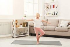 Den gulliga lilla flickan som gör yoga, övar hemma royaltyfria foton