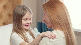 Den gulliga lilla flickan som kramar hennes moder med hennes ögon, stängde sig stock video