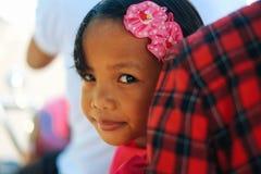 Den gulliga lilla flickan som ler i rosa färger, klär den hållande buketten för vita blommor på bröllopberöm Liten brudtärna på b Royaltyfri Foto