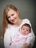 Den gulliga lilla flickan som rymmer ett nyfött, behandla som ett barn royaltyfri fotografi
