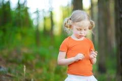 Den gulliga lilla flickan som spelar `, älskar mig? älskar mig inte? lek för `-tusenskönakronblad Arkivfoto