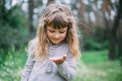 Den gulliga lilla flickan som spelar i gräsplan, parkerar Arkivbild