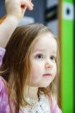 Den gulliga lilla flickan som studing till att tala och att skriva, märker hemma Royaltyfri Bild