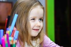 Den gulliga lilla flickan som studing till att tala och att skriva, märker hemma Royaltyfri Foto