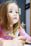 Den gulliga lilla flickan som studing till att tala och att skriva, märker hemma Arkivfoto