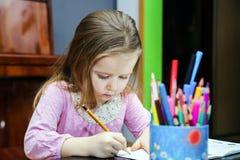 Den gulliga lilla flickan som studing till att tala och att skriva, märker hemma Arkivbild