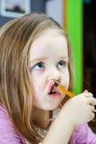 Den gulliga lilla flickan som studing till att tala och att skriva, märker hemma Arkivfoton