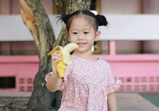 Den gulliga lilla flickan som ?ter bananen i, parkerar arkivbilder