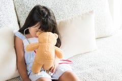 Den gulliga lilla flickan spelar doktorn med stetoskopet och nallebjörnen royaltyfria foton