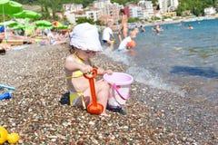 Den gulliga lilla flickan spelar med hinken på en strand Royaltyfri Fotografi