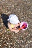 Den gulliga lilla flickan spelar med hinken på en strand som samlar r Royaltyfri Foto
