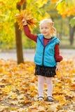 Den gulliga lilla flickan spelar med sidor i höst parkerar arkivbild