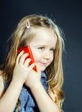Den gulliga lilla flickan talar genom att använda den nya mobiltelefonen Arkivfoto