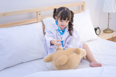 Den gulliga lilla flickan tycker om att spela doktorn med doktorsleksakuppsättningen Arkivfoton