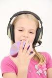 Den gulliga lilla flickan tycker om musik genom att använda hörlurar Royaltyfri Foto