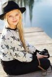 Den gulliga lilla flickan vilar nära sjön med kameran Arkivbilder