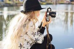 Den gulliga lilla flickan vilar nära sjön med kameran Arkivbild