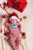 Den gulliga lilla jultomten behandla som ett barn att posera bredvid julgranen på slags tvåsittssoffahemmet med garnering för det Royaltyfri Foto