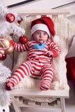 Den gulliga lilla jultomten behandla som ett barn att posera bredvid julgranen på slags tvåsittssoffahemmet med garnering för det Arkivfoto