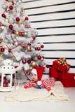 Den gulliga lilla jultomten behandla som ett barn att posera bredvid julgranen på slags tvåsittssoffahemmet med garnering för det Royaltyfri Fotografi