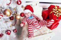 Den gulliga lilla jultomten behandla som ett barn att posera bredvid julgranen på slags tvåsittssoffahemmet med garnering för det Royaltyfria Foton