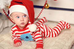 Den gulliga lilla jultomten behandla som ett barn att posera bredvid julgranen på slags tvåsittssoffahemmet med garnering för det Arkivbild