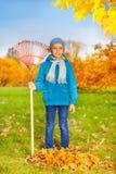 Den gulliga lilla pojken med krattar ställningar för att göra ren gräs Royaltyfri Fotografi