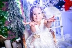 Den gulliga lilla prinsessan i en vit klänning sitter på en släde, snöar kast upp och skratt arkivfoto