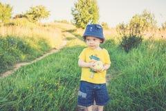 Den gulliga lilla ungen har äpplet i hand royaltyfri fotografi