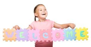 Den gulliga liten flicka är holdingvälkomnandeslogan arkivfoto