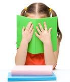 Den gulliga liten flicka döljer bak en bok arkivbild