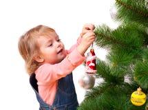 Den gulliga liten flicka dekorerar julgranen royaltyfri foto
