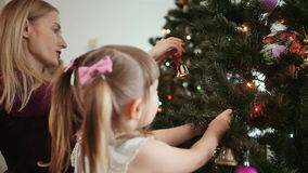 Den gulliga liten flicka dekorerar julgranen arkivfilmer