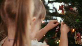 Den gulliga liten flicka dekorerar julgranen stock video