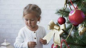 Den gulliga liten flicka dekorerar julgranen lager videofilmer