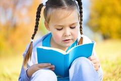 Den gulliga liten flicka läser en bok royaltyfria foton