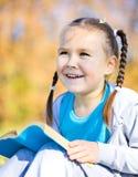 Den gulliga liten flicka läser en bok royaltyfri fotografi
