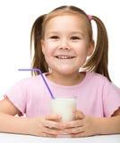 Den gulliga liten flicka med ett exponeringsglas av mjölkar royaltyfria foton