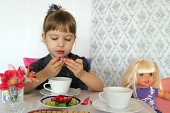 Den gulliga liten flicka som leker med dockan royaltyfria bilder