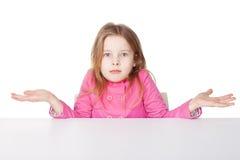 Den gulliga liten flicka som rycker på axlarna henne, knuffar Arkivbild
