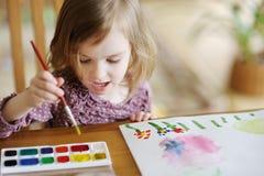 Den gulliga liten flicka tecknar med målarfärger Royaltyfri Fotografi