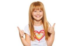 Den gulliga liten flickavisningen tummar upp med båda händer som isoleras på vit arkivfoton